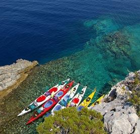 Kayak accosté, au bord d'une mer turquoise.