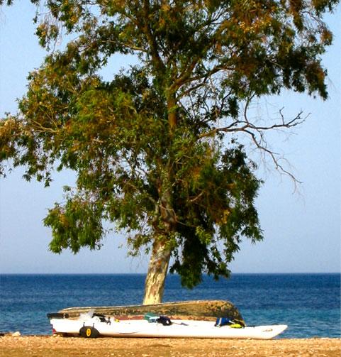 Photos de la Grèce : Des kayaks échoués sur une plage déserte au bord d'une mer aux eaux turquoises.